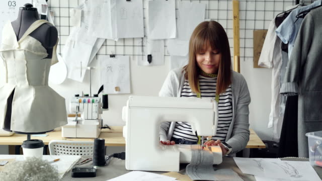 Young-attractive-dressmaker-is-working-on-sewing-machine-and-looking-at-women-s-garment-sketches-in-her-studio-at-table-Modern-equipment-and-fashionable-garments-in-background-