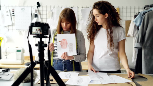Young-women-fashion-bloggers-recording-video-blog-about-ladies-clothes-on-camera-and-talking-to-followers-in-modern-studio-Many-garment-sketches-are-visible-