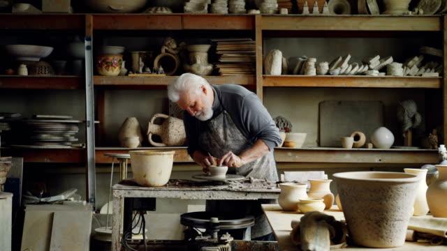 Ceramista-experimentado-está-creando-utensilios-de-arcilla-en-el-torno-de-alfarero-en-taller-Producción-de-eathenware-hecho-a-mano-utensilios-y-cerámica-profesional-concepto-