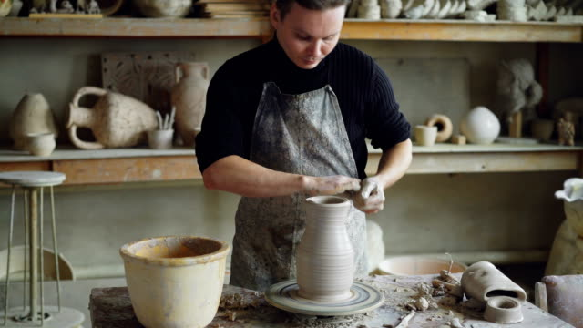 Hombre-joven-guapo-es-moldeado-florero-de-cerámica-de-la-arcilla-en-spinning-lanzando-la-rueda-mientras-trabajaba-en-el-estudio-de-potter-Profesional-se-concentra-en-el-trabajo-