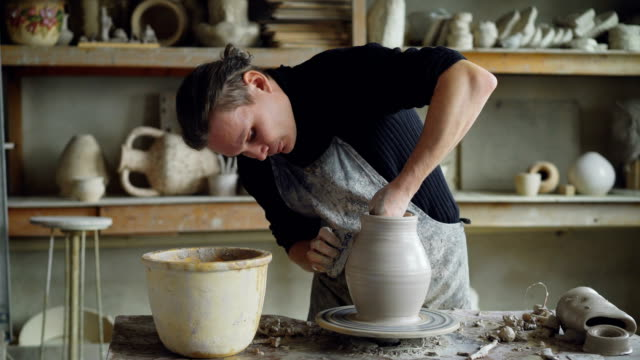 Skillful-young-potter-is-molding-ceramic-vase-from-clay-on-turning-throwing-wheel-while-working-in-potter-s-workshop-Professional-is-concentrated-on-work-