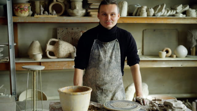 Portrait-of-handsome-young-potter-in-muddy-apron-standing-at-table-in-workshop-and-looking-at-camera-Shelves-with-handmade-vases-and-pots-in-background-