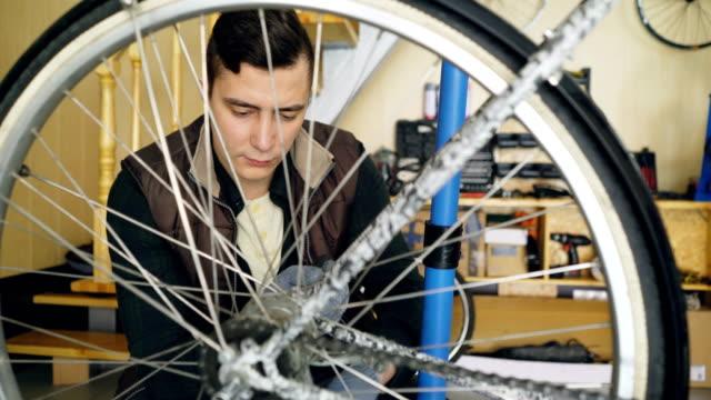 Hombre-mecánico-profesional-es-reparando-la-rueda-de-bicyce-en-trabajo-moderno-con-piezas-de-repuesto-y-equipo-especial-Mantenimiento-personas-y-el-concepto-de-pequeña-empresa-
