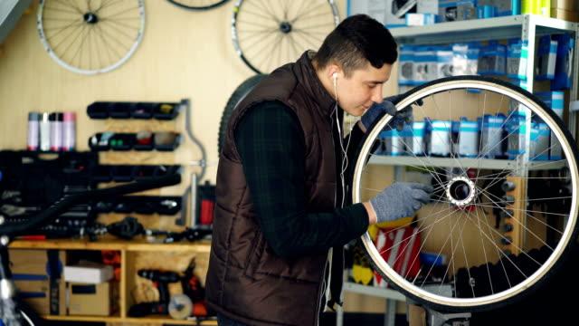 Joven-técnico-es-limpieza-de-rueda-de-bicicleta-dentro-y-fuera-con-herramientas-y-piezas-de-tela-y-escuchando-música-con-auriculares-Concepto-de-profesión-y-personas-