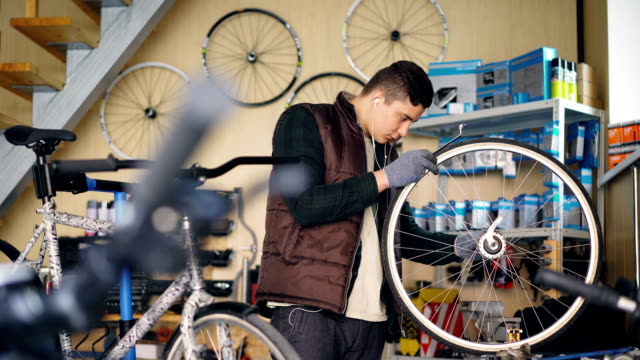 Self-employed-mechanic-is-repairing-bicycle-wheel-with-wrenches-professional-instruments-while-working-in-small-workshop-Young-man-is-listening-to-music-with-earphones-