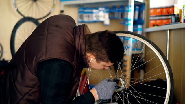 Mantenimiento-joven-hombre-es-fregar-la-suciedad-de-la-rueda-de-bicicleta-limpiarla-con-un-trozo-de-tela-y-tratamiento-con-aerosol-Concepto-de-mantenimiento-y-personas-bicicleta-