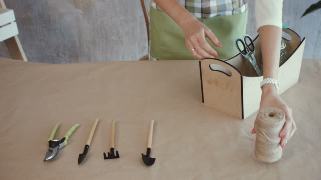 Florist-hands-laying-out-floristic-tools-on-table
