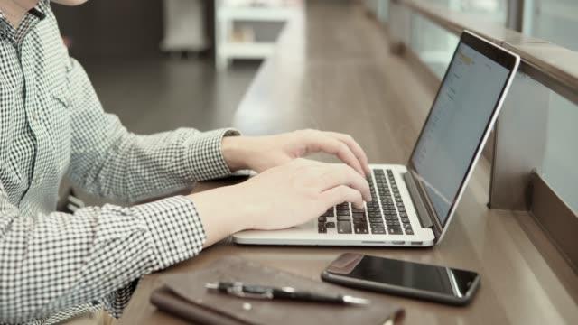 Junge-asiatische-Geschäftsmann-mit-Laptop-Computer-im-Arbeitsraum-mit-Smartphone-und-Notebook-am-Schreibtisch-aus-Holz-Männliche-Hand-auf-Laptoptastatur-tippen-Freiberuflicher-Lebensstil-im-digitalen-Zeitalter-Konzept-