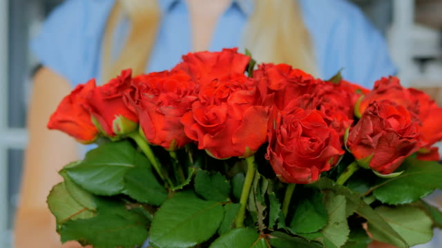 Professional-florist-preparing-red-roses-for-bouquet-at-workshop