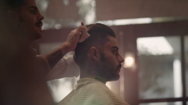 Young-stylish-barber-with-tattoos-cutting-and-styling-man-s-hair