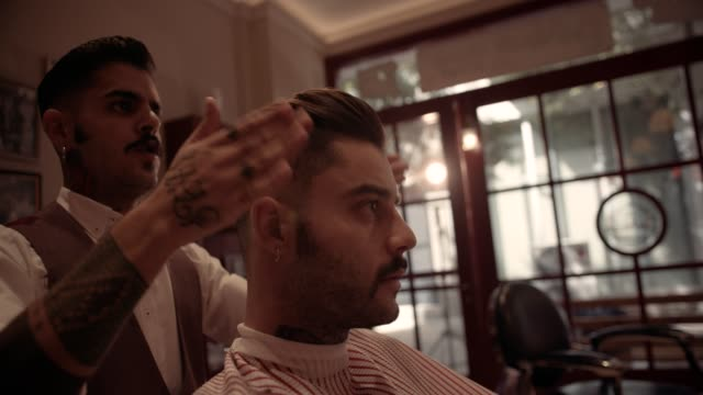 Barber-styling-man-s-hair-after-haircut-in-old-fashioned-barber-shop