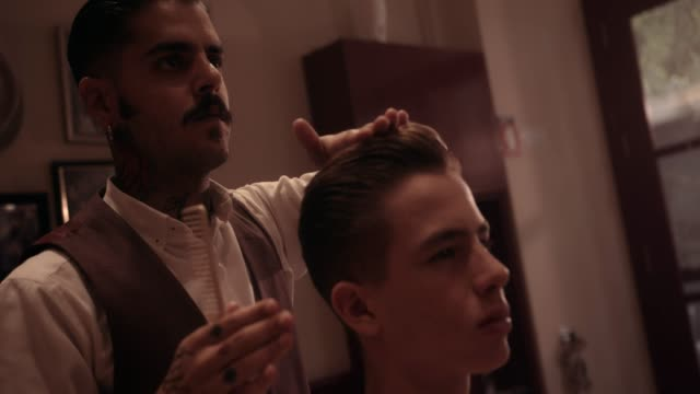 Hipster-hairdresser-styling-young-man-s-hair-at-old-fashioned-barber-shop