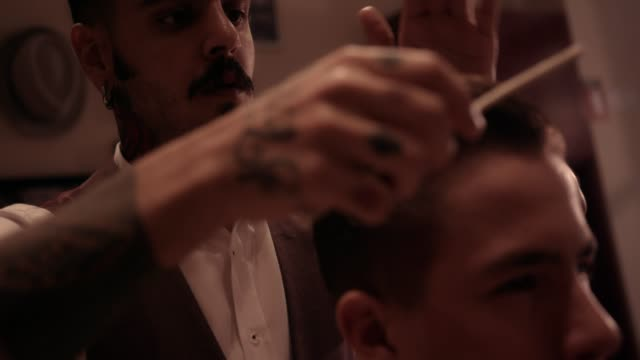 Young-stylish-hairdresser-with-tattoos-and-mustache-styling-man-s-hair