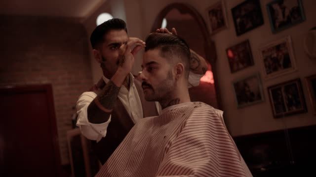 Hipster-hairdresser-styling-customer-s-hair-at-old-fashioned-barber-shop
