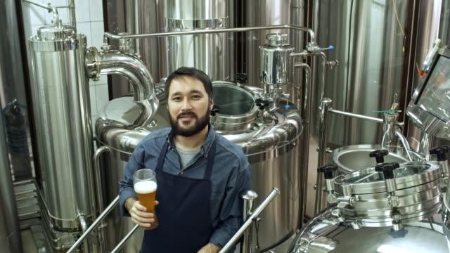 Brauerei-Worker-posiert-mit-Glas-Bier