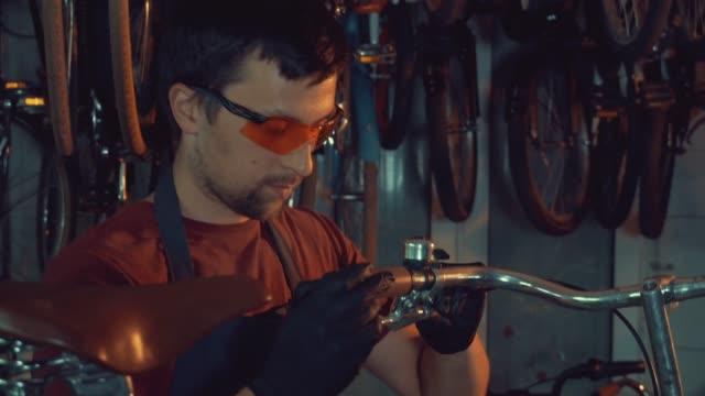 Thema-Kleinunternehmen-Fahrradreparatur-Ein-junger-kaukasischen-Brünette-Mann-mit-Sicherheit-Schutzbrillen-Handschuhe-und-eine-Schürze-nutzt-ein-Handwerkzeug-zu-reparieren-und-stellen-das-Fahrrad-in-der-Garage-Werkstatt
