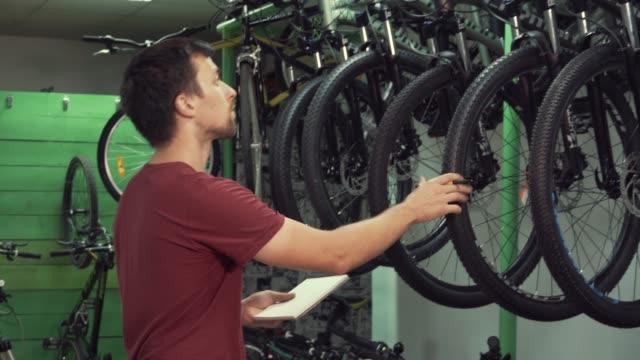 tema-de-pequeño-negocio-de-venta-de-bicicletas-Joven-caucásica-hombre-morena-microempresaria-Gerente-de-la-tienda-utiliza-Bloc-de-notas-y-pluma-hace-notas-lista-de-verificación-en-la-tienda-de-bicicletas