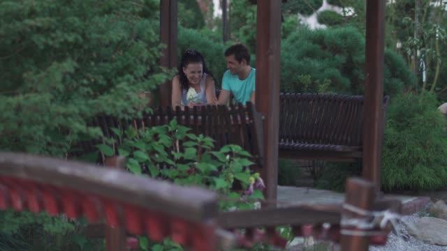 Chico-y-una-chica-están-sentados-en-el-Parque
