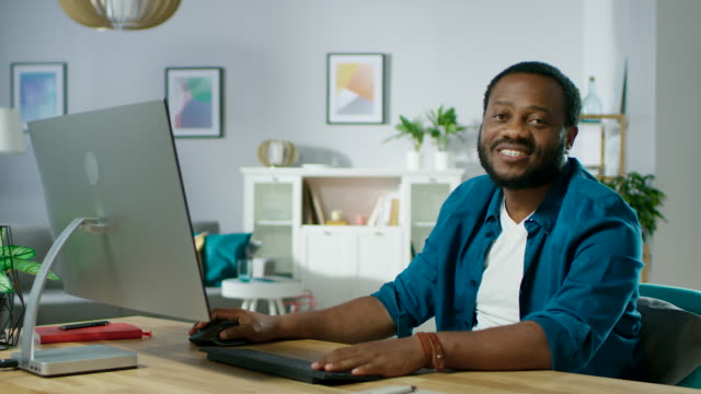 """Enthält-Audio:-Schöner-erfolgreicher-Mann-nutzt-PC-zu-Hause-sieht-in-die-Kamera-mit-einem-Lächeln-und-sagt:-\""""Vielen-Dank-für-das-ansehen\""""-"""