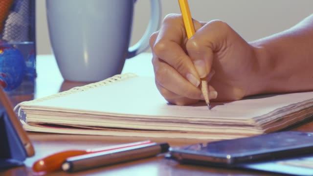 Tiro-de-carro-de-la-mujer-que-trabaja-en-casa-oficina-escribiendo-en-cuaderno-a-mano