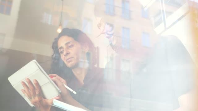 Zwei-Geschäftsfrauen-Brainstorming-zusammen-mit-elektronischen-Gerät-auf-eine-lockere-und-freundliche-Besprechung