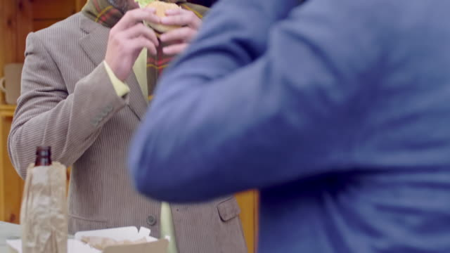 Stylish-man-chewing-burger-beside-street-cafe