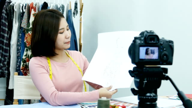 Female-fashion-bloggers-present-about-her-work-to-camera-and-talking-to-followers-in-modern-studio-People-with-creativity-fashion-designer-concept-