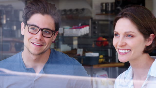 Three-young-adult-friends-talking-and-smiling-at-coffee-shop