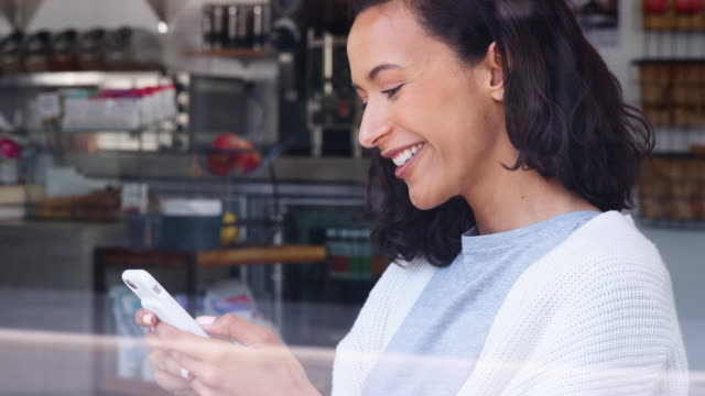 Young-female-using-her-smartphone-at-a-coffee-shop