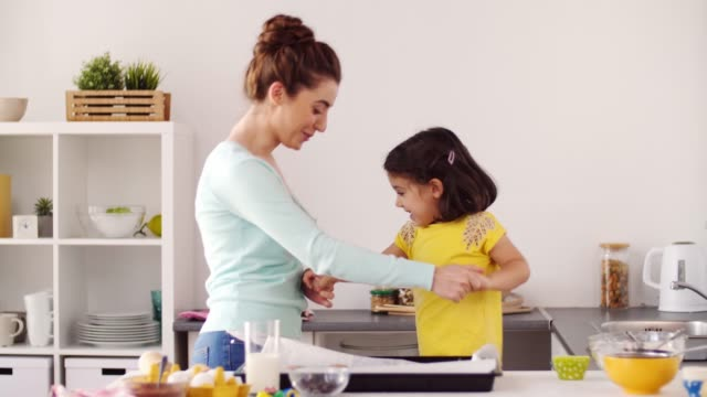 mother-with-daughter-cooking-and-dancing-at-home