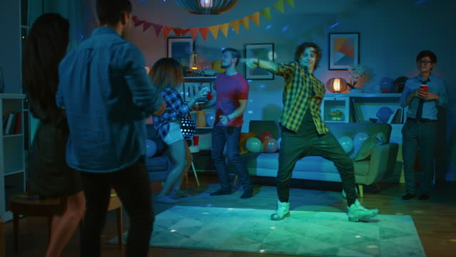 At-the-College-House-Party:-Diverse-Group-of-Friends-Have-Fun-Dancing-and-Socializing-One-Guy-Does-Robot-Dance-Moves-Girls-Cheer-Boys-and-Girls-Dance-in-the-Circle-Disco-Neon-Strobe-Lights-