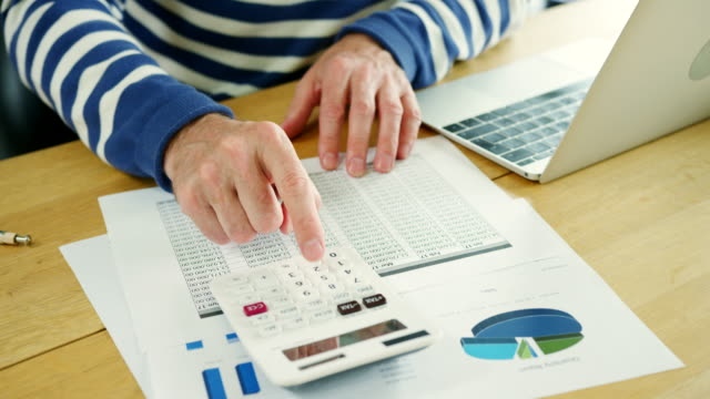 Businessman-Analysing-And-Calculation-Financial-Data-At-His-Desk