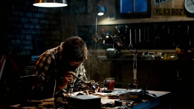 Man-soldering-drone-in-a-garage