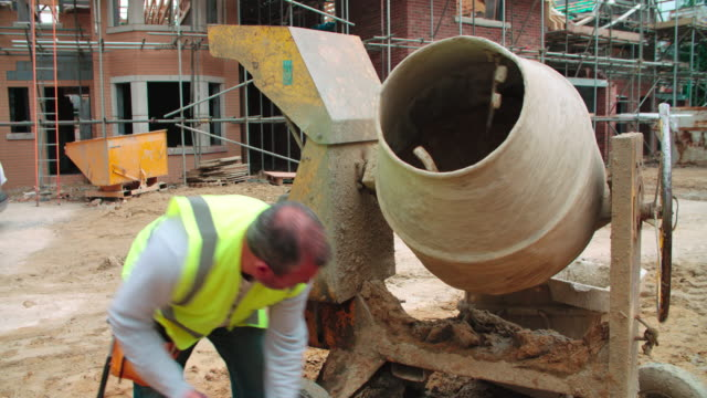 Construction-Worker-On-Building-Site-Mixing-Cement