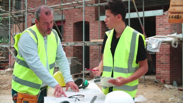 Builder-On-Site-Discussing-Work-With-Male-Apprentice