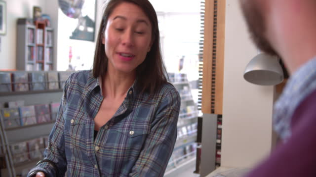 Young-woman-paying-at-the-counter-of-a-record-shop-close-up