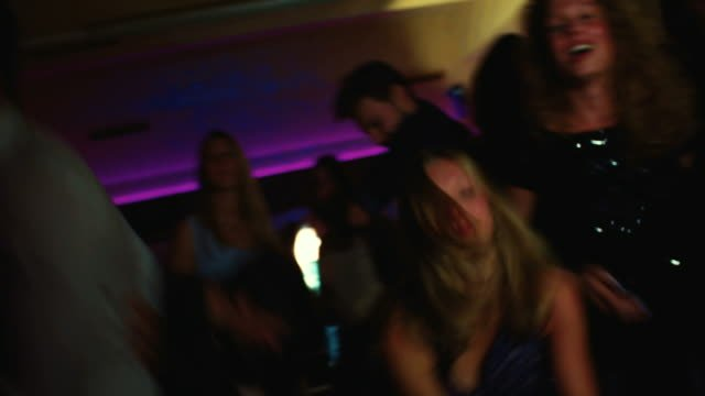 Friends-dancing-and-singing-together-happily-at-a-party
