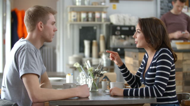 Adult-couple-talking-at-a-table-in-a-coffee-shop-side-view