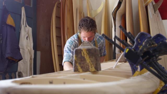 Man-Shaping-Custom-Surfboard-In-Workshop-Shot-On-RED-Camera