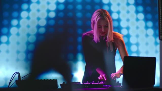 DJ-mujer-rubia-bailando-detrás-de-mezclador