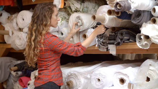 Young-woman-selecting-fabric-from-rolls-on-storage-shelves