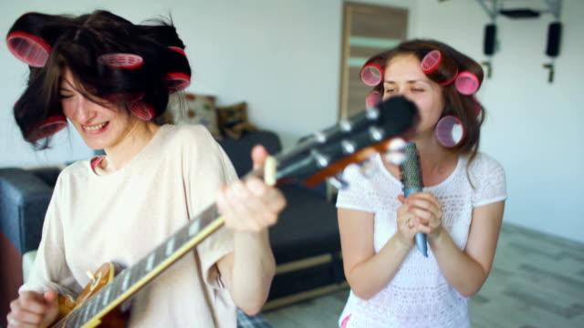 Dos-chicas-divertidas-cantando-con-el-peine-y-tocando-el-baile-de-la-guitarra-eléctrica-cantan-y-tienen-alegría-en-casa