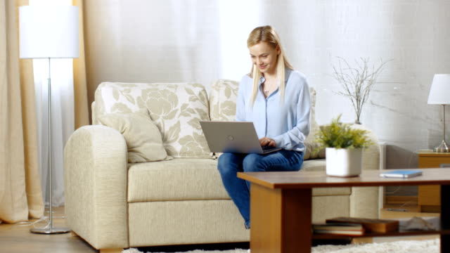 Smiling-Young-Woman-Working-on-a-Laptop-She-s-in-Her-Living-Room-Sitting-on-a-Sofa-and-Holding-Notebook-on-Her-Lap-