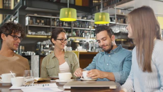 Pequeño-equipo-creativo-de-jóvenes-activos-que-tienen-reunión-y-discusión-en-la-cafetería-