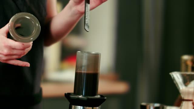 Barista-preparing-black-coffe-with-aeropress