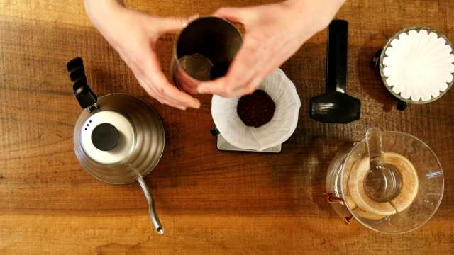 Hand-drip-coffee-barista-pouring-water-on-coffee-ground-with-filter