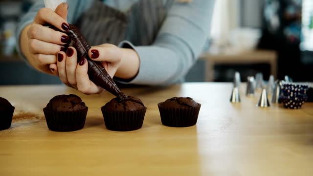 Nahaufnahme-der-weiblichen-Hände-legt-die-Creme-aus-Spritzbeutel-auf-Schokoladen-Cupcakes-Junge-Frau-die-kochen-die-muffins