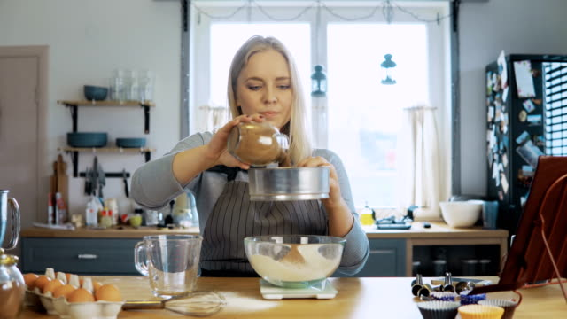 Young-beautiful-woman-weighs-the-cocoa-adds-to-flour-Girl-using-kitchen-scales-bowl-and-sieve-for-this