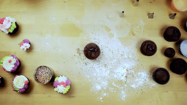 Draufsicht-der-jungen-weiblichen-Händen-Verzierung-die-Schokolade-Cupcake-oder-Muffin-mit-Sahne-mit-Spritzbeutel-für-diese