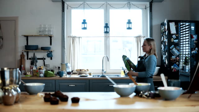 Young-beautiful-woman-washing-the-bowl-after-baking-the-cupcakes-Blonde-female-cleaning-the-kitchen-after-cooking